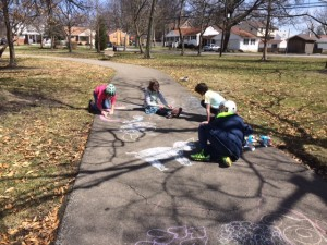 A photo of my two and some friends drawing inspirational messages on the sidewalk at a local park.